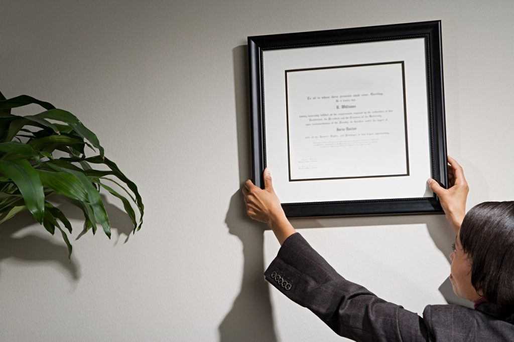 Employee hanging a certificate