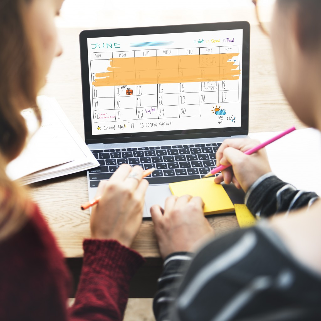 People planning out schedule on online calendar